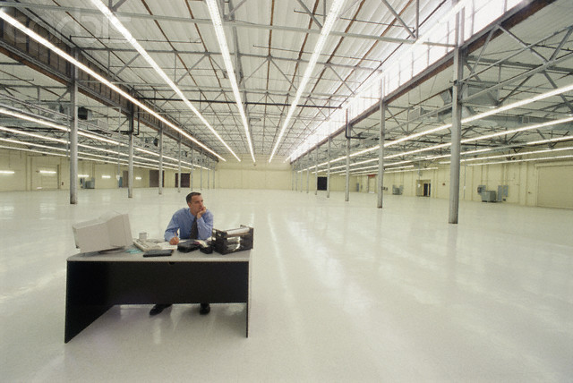 Man at Lonely Desk in Warehouse